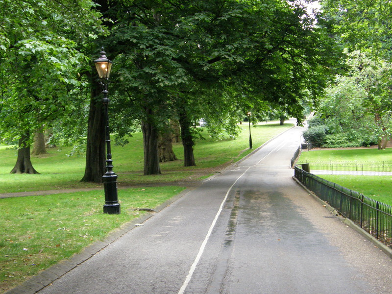 A path in Hyde Park with a lit gaslight