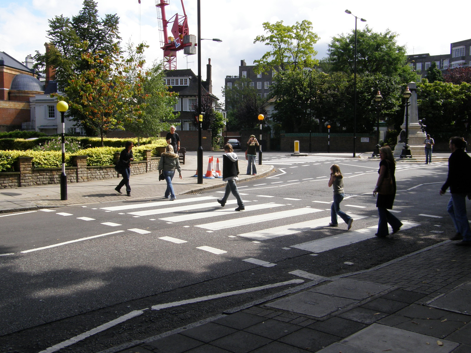 Tourists walking across the famous Abbey Road zebra crossing